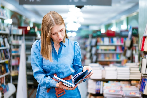 書店や書店のベストセラーを読んで開いている紙の本を持っている女性のかわいいビューを楽しんでいます...
