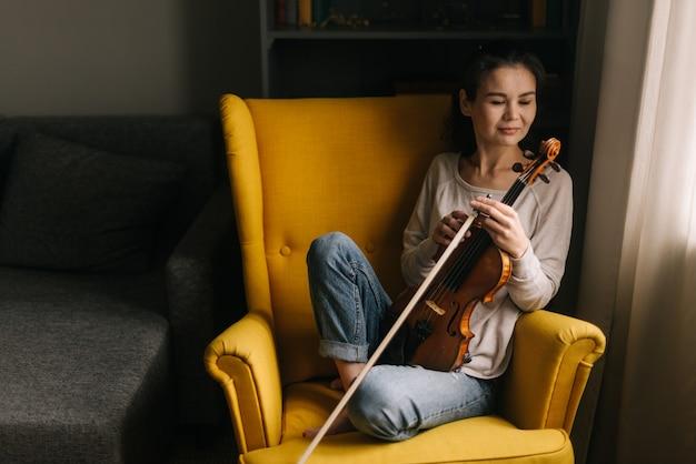 Симпатичная подруга скрипача сидит со скрипкой в мягком кресле дома и смотрит вниз. девушка позирует с музыкальным инструментом.
