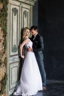 飾られた古典的なスタジオのインテリアでかわいい結婚式のカップル。彼らはお互いにキスして抱擁します。