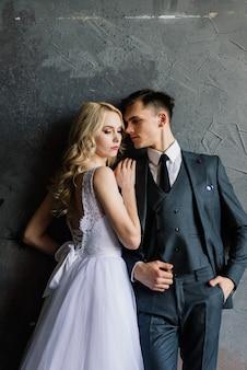 飾られた古典的なスタジオのインテリアでかわいい結婚式のカップル。彼らはお互いにキスをし、抱き合います。