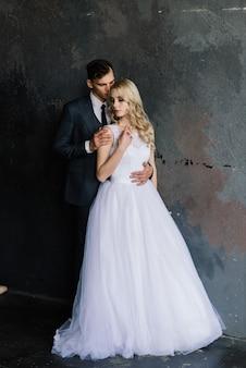 飾られた古典的なスタジオのインテリアでかわいい結婚式のカップル。