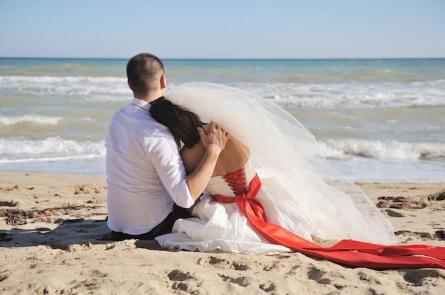 ビーチの砂の上に座っているかわいい結婚式のカップル、背中、顔なし