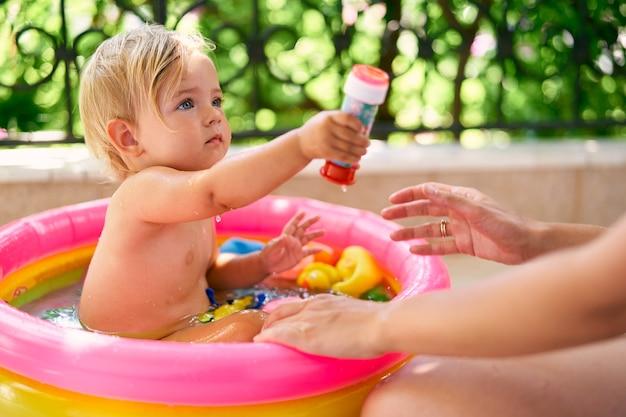 귀여운 젖은 아기는 장난감이 있는 작은 풍선 수영장에 앉아 있습니다.