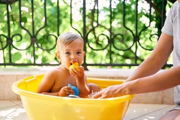 귀여운 젖은 아이는 대야에 앉아서 장난감을 g아 먹는다