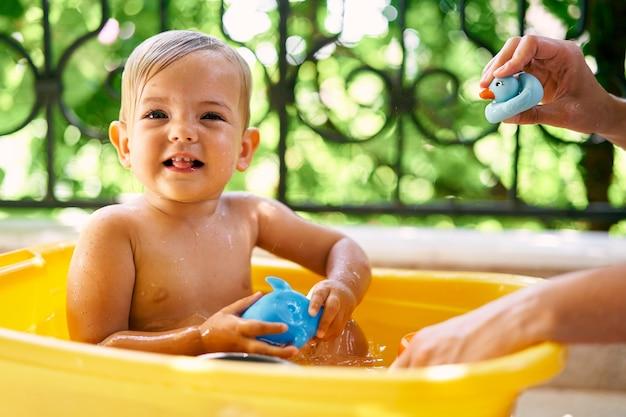 귀여운 젖은 아이는 대야에 앉아서 장난감을 가지고 있습니다