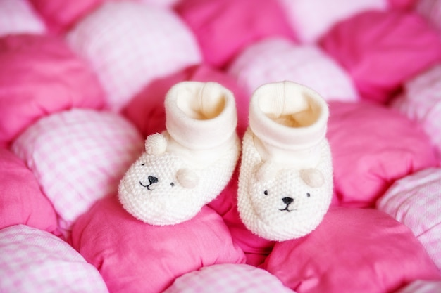 Cute white baby booties on pink blanket. pregnancy concept