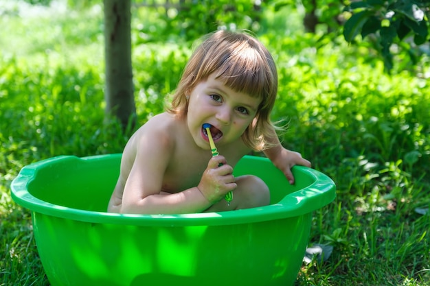 Cute white baby girl bathing and holding toothbrush in small bathtub