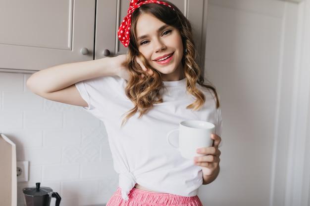 お茶と一緒にキッチンに立っているカジュアルなtシャツのかわいい白人の女の子。朝のコーヒーを飲むリラックスした女性モデルの屋内ショット。