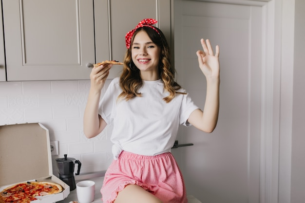 Cute white girl with ribbon in hair sitting in kitchen with smile. gorgeous european lady eating pizza with happy face expression.