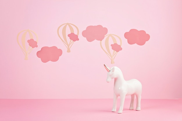 Cute white unicorn over the pink pastel background with clouds and baloons