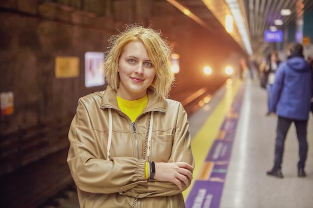 かわいい白人の若い女性が電車を待って、地下鉄の駅のホームに立っています。