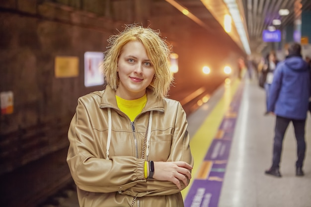 Cute white young woman stands on subway station platform, waiting for train.