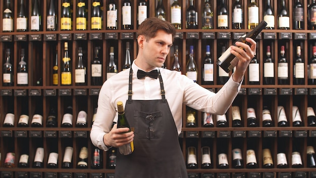 Cute wine seller holds bottles of wine and reads the label in a wine store. helps you choose