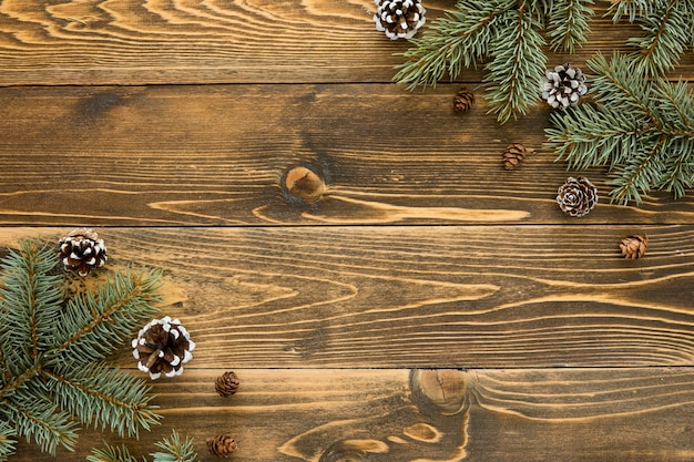 Cute winter pine needles and cones on wooden background