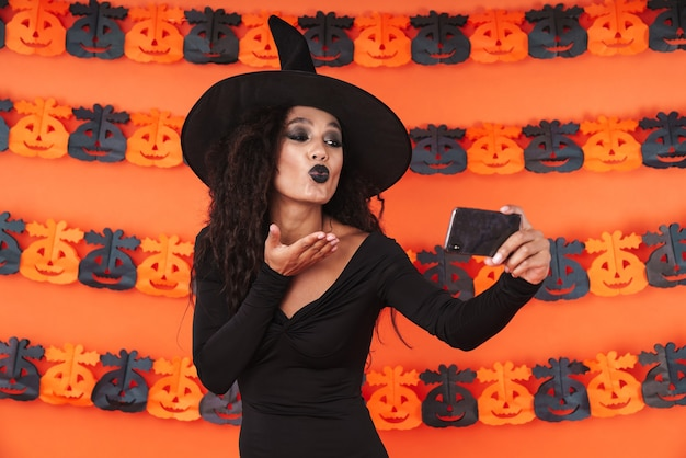 Cute witch girl in black halloween costume taking selfie photo on smartphone with kissing isolated over orange pumpkin wall