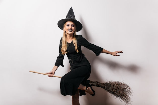 Cute witch in long dress sitting on broom with smile. carefree blonde lady in carnival costume enjoying halloween.