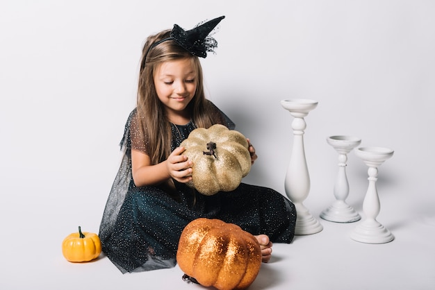 Cute witch playing with pumpkins