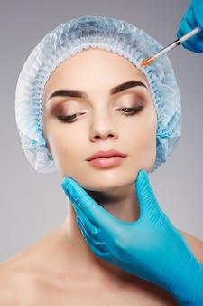 Симпатичный с обнаженным макияжем на фоне студии, руки врача в синих перчатках возле лица пациента, концепция красоты, шприц botex возле лица.