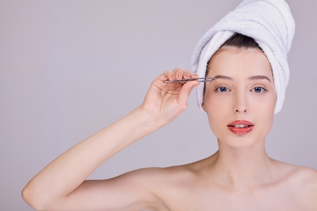 A cute woman after a shower plucks her eyebrows with tweezers.