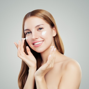 Милая женщина, применяя крем на здоровую кожу и улыбается