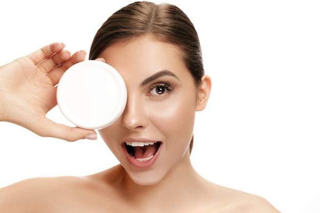 Cute woman applying moisturizer cream on face at studio