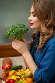 果物と野菜の背景にブロッコリーを保持しているテーブルでかわいい女性