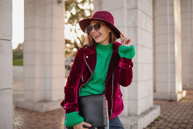 Cute woman in autumn style trendy outfit walking in street
