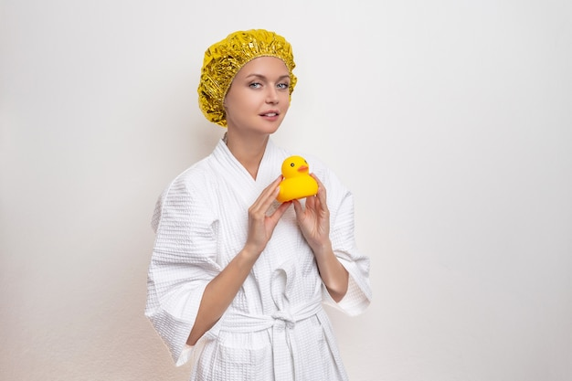 Cute woman in a bathrobe and a golden shower cap on her head poses