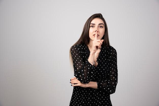 Cute woman in black dress making silence sign.