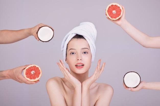 Cute woman chooses between coconut and grapefruit.