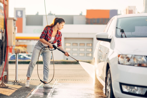 Милая женщина чистит автомобильные колеса с помощью водяного пистолета под высоким давлением.