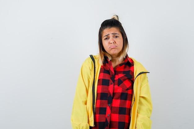 シャツ、ジャケットの下唇を湾曲させ、失望しているように見える、正面図のかわいい女性。