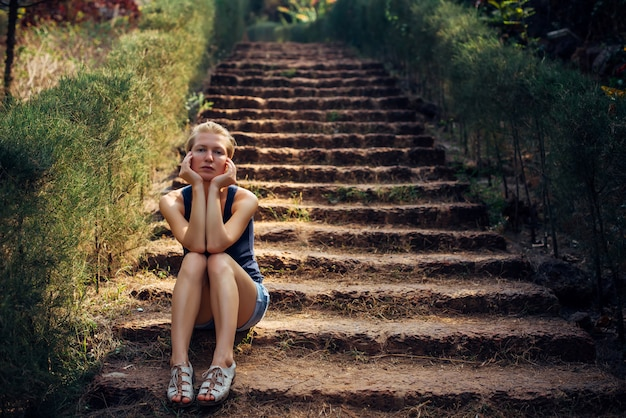 Cute woman in denim shorts sitting on step of the stairs in summer park.