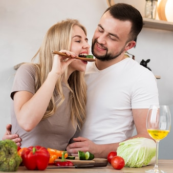 Cute woman eating cucumber with her man