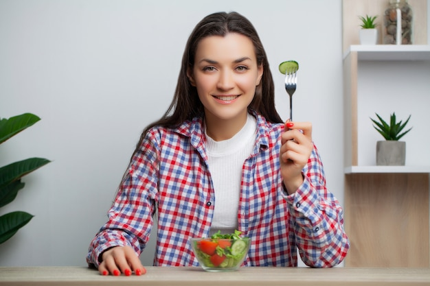 Cute woman eats vegetable salad with lots of vitamins.