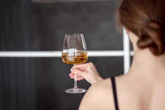 白ワインのグラスを楽しんでいるかわいい女性