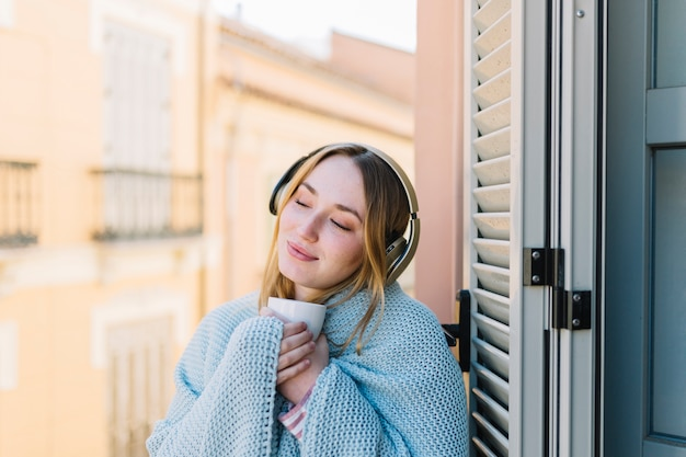 Cute woman enjoying music on balcony