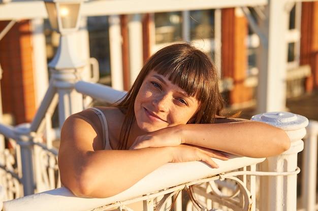 かわいい女性は、都市のフェンスに彼女の腕をもたれ、夕日の光を楽しんでいます