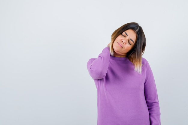 Cute woman feeling neck pain in purple sweater and looking tired , front view.