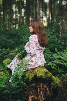 A cute woman in a floral dress is sitting with a fern bouquet in the forest.