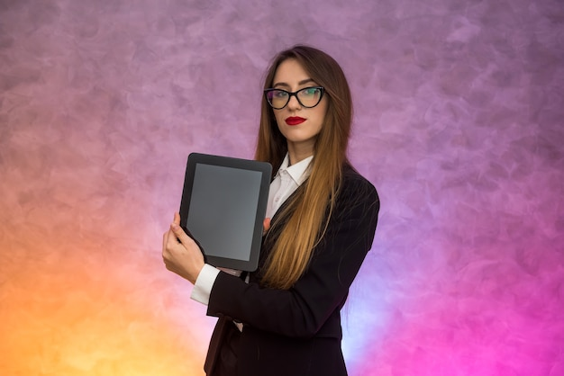 Cute woman in glasses using tablet on abstract background. business concept