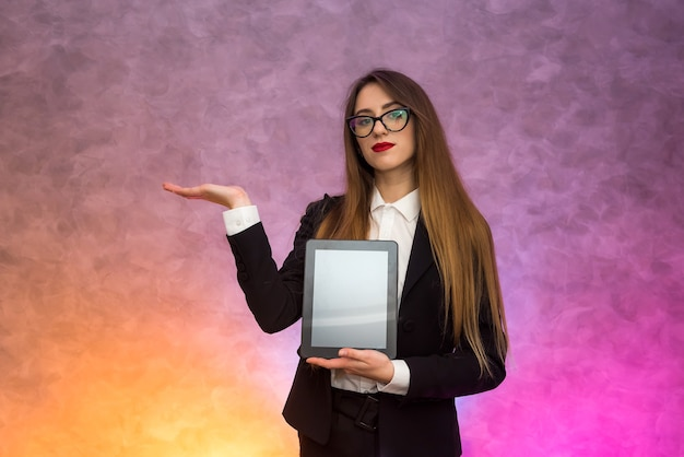Cute woman in glasses using tablet on abstract wall