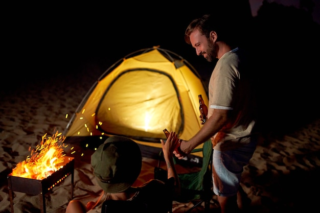 A cute woman and a handsome man are sitting on folding chairs near the tent by the fire, drinking beer and having fun at night on the beach by the sea.