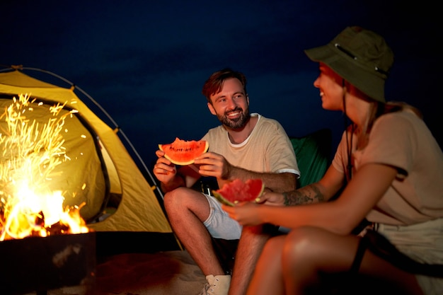 A cute woman and a handsome man are sitting on folding chairs near the tent by the fire, eating watermelon and having fun at night on the beach by the sea.