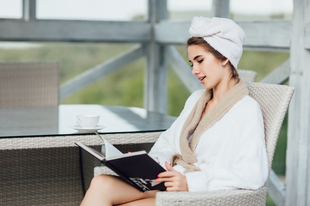 귀여운 여성은 주말에 고급 여름 테라스에서 책을 읽고 있습니다.