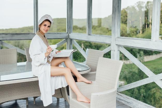 かわいい女性は、豪華なサマーテラスでお茶を飲みながらテーブルに座っている間、週末と読書本を持っています。ビューティービュー。