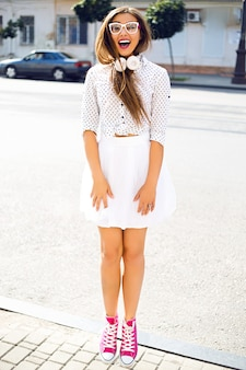 Милая женщина веселится на улице в белом забавном платье и белых наушниках