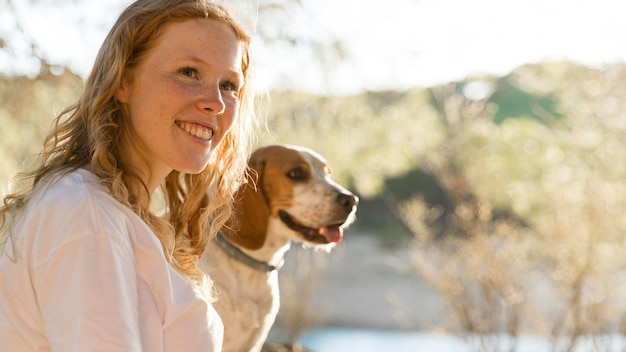 Cute woman and her dog in the nature