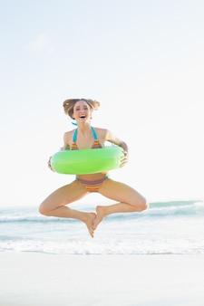 해변에서 점프하는 동안 고무 링을 들고 귀여운 여자