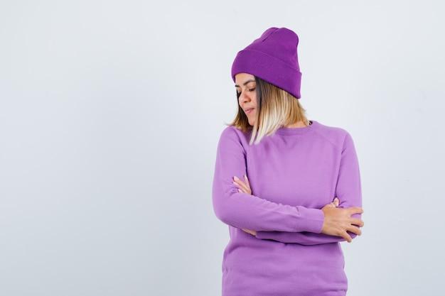 Donna carina che tiene le braccia conserte, chiude gli occhi in maglione, berretto e sembra delicata. vista frontale.